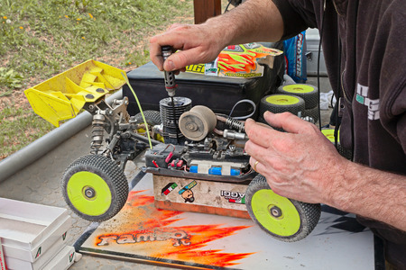 off track: man working on the radio controlled buggy car model, internal combustion engine, in regional championship scale 18 off road in dirt track Il Pozzo on April 26, 2015 in Riolo Terme, RA, Italy