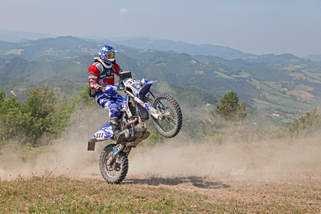 scrambler: biker riding enduro motorcycles Yamaha WRF 450 in the green mountain during the Italian championship Motorally Terre di Romagna, on July 5, 2015 in Predappio, FC, Italy Editorial