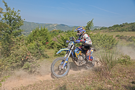 scrambler: biker riding enduro motorcycles Husaberg 390 in the green hills during the Italian championship Motorally Terre di Romagna, on July 5, 2015 in Predappio, FC, Italy
