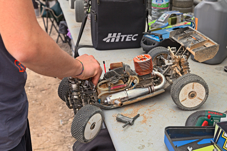 4wd: man working on the radio controlled buggy car model, internal combustion engine, in regional championship scale 18 off road in dirt track Il Pozzo on April 26, 2015 in Riolo Terme, RA, Italy