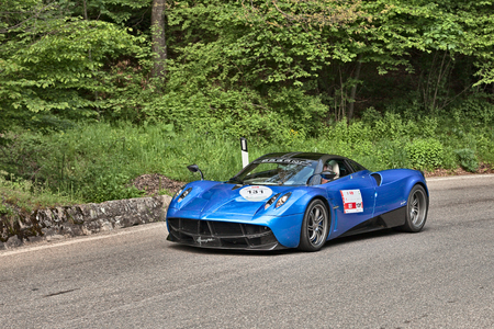 sports race: driver and co-driver on a sports car Pagani Huayra travel in historical italian race Mille Miglia on May 18, 2013 in Passo della Futa FI Italy Editorial