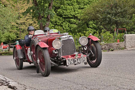 sports race: driver and co-driver on an old sports car Aston Martin International Le Mans 1931 in the italian historic race Mille Miglia, on May 18, 2013 in Passo della Futa FI Italy