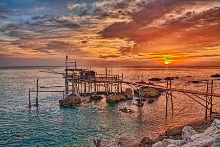 shanty: Adriatic sea coast at sunrise in Chieti, Abruzzo, Italy, with an ancient fishing hut trabocco, the typical mediterranean wooden pilework