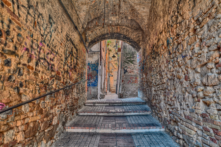 graffito: dark underpass and narrow alley in the old italian town -  typical walkway in ancient city of Italy