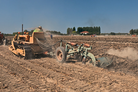 santagata: farmer plowing the field with an old crawler tractor Fiat and the plow during the country fair Rombi agricoli on August 30, 2015 in SantAgata sul Santerno, Ravenna, Italy Editorial