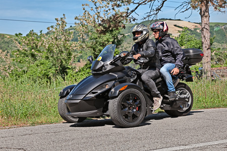 three wheeler: biker riding three-wheeled vehicle BRP Can-Am Spyder Roadster in motorcycle rally Mototagliatella on May 10, 2015 in Predappio, Italy