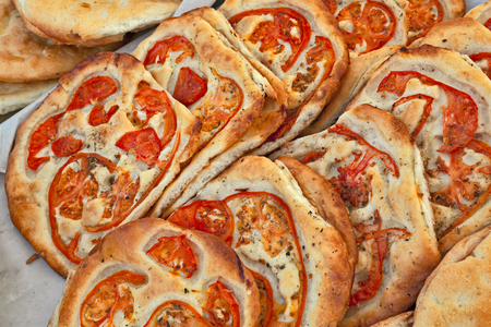 ovenbaked: Italian food: traditional focaccia (schiacciata of Tuscany) with tomato, a flat oven-baked bread product with olive oil, very popular in Italy. Similar to pizza doughs but more soft and thick and often with addition of spices and vegetables Stock Photo