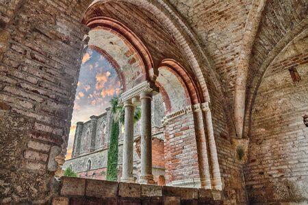 abandoned: view of the medieval abbey in ruins through the ancient mullioned window from the monastery of San Galgano in Siena, Tuscany, Italy