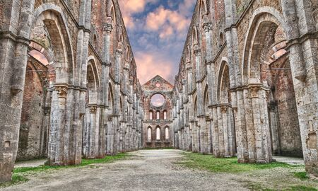 abbazia: nave with the majestic colonnade of the medieval roofless cathedral in ruins of San Galgano in Siena, Tuscany, Italy Stock Photo