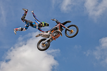 freestyle motocross show; a stunt biker make a jump and performing an acrobatic figure in flight, during the motorcycle rally Motosalsicciata 2016 on April 10, 2016 in Voltana di Lugo (RA) Italy