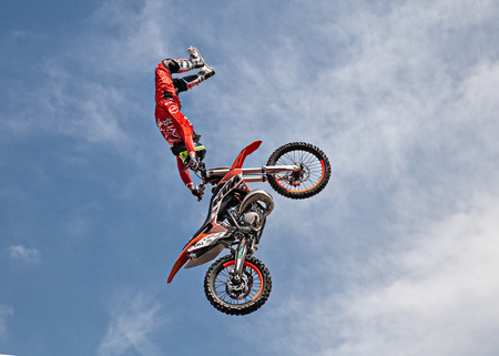 motosport: VOLTANA DI LUGO (RA) ITALY - APRIL 10: freestyle motocross show; a stunt biker make a jump and performing an acrobatic figure in flight, during the motorcycle rally Motosalsicciata 2016 on April 10, 2016 in Voltana di Lugo (RA) Italy Editorial