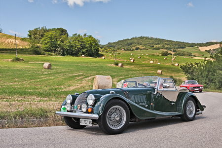 """driver and co-driver on a vintage car Morgan 2.0 traveling in the hills during the rally """"Colline di Romagna"""" on July 3, 2016 in Tredozio, FC, Italy"""