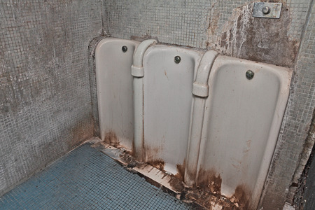 unsightly: public restroom with dirty and fouling old urinals Stock Photo