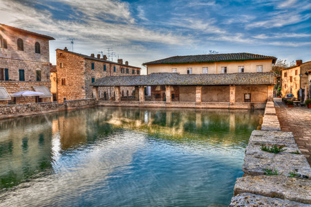 water town: Bagno Vignoni, Siena, Tuscany, Italy: old thermal baths at dawn in the medieval village; vapor over the water in the square of sources, spa basin in the ancient italian town Stock Photo