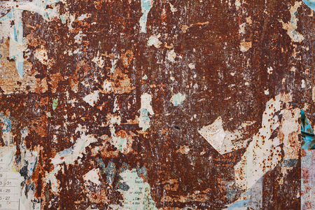 old texture: grunge ripped poster on rusty iron sheet background - texture of torn advertisement on an old rusty billboard panel
