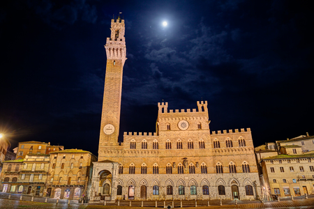 Siena, Tuscany, Italy: the ancient town hall Palazzo Pubblico and the tower Torre del Mangia in the city square Piazza del Campo at night with moon