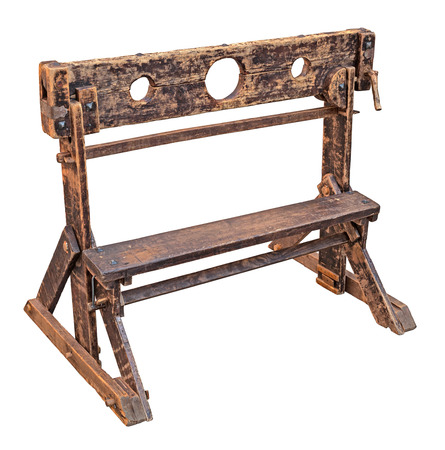 immobilize: medieval pillory, ancient device used for punishment by public humiliation and physical abuse - old wooden stocks isolated with clipping path