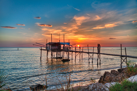 shanty: Chieti, Abruzzo, Italy: Adriatic sea coast at sunrise with an ancient fishing hut trabocco, the typical mediterranean wooden pilework Stock Photo