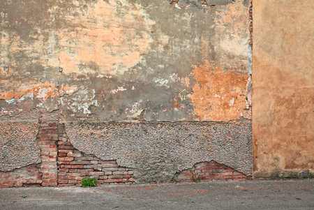 urban decay: old wall with peeling paint and scratched stained plaster - grunge orange pastel background of urban decay