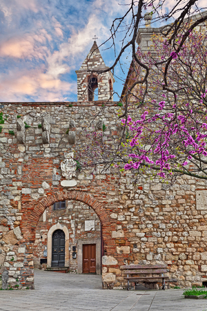 leghorn: Rosignano Marittimo, Leghorn, Tuscany, Italy: old alley and stone wall with the entrance door to the courtyard of the medieval castle and church Editorial