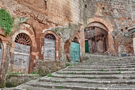 old doors: Pitigliano, Tuscany, Italy: old stairway, cellar doors and medieval city door Porta di Sovana in the village founded in Etruscan times Stock Photo