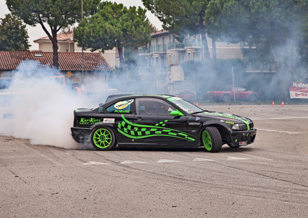 vincoli: driver and co-driver on a drift racing car BMW in action drifting with smoking tires  in Telethon Motor Show on October 23, 2016 in San Pietro in Vincoli, Ravenna, Italy Editorial