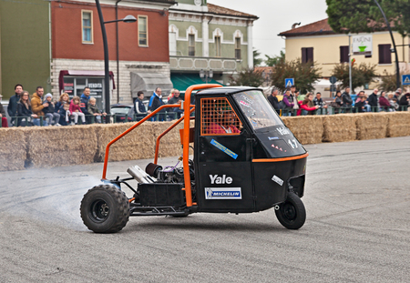 engine powered: driver drifting on a three-wheeled Italian vehicle Ape Piaggio powered with Kawasaki GPZ engine in Telethon Motor Show on October 23, 2016 in San Pietro in Vincoli, Ravenna, Italy