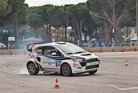 engine powered: driver on a powerful racing car Mitsubishi Colt 4WD with Evo engine 530 hp power in action with smoking tires in Telethon Motor Show on October 23, 2016 in San Pietro in Vincoli, Ravenna, Italy Editorial