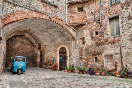 three wheeler: a picturesque old alley with dwellings and an ancient italian vehicle Ape Piaggio, on September 10, 2013 in Todi, Umbria, Italy Editorial