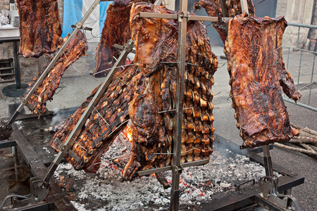 barbecue: An asado is a roasted meat of beef or various other meats, which are cooked on a typical barbecue with vertical grills placed around at fire and embers in a big brazier. It is a traditional dish in Argentina, Uruguay, Paraguay, Chile, and Brazil. Stock Photo