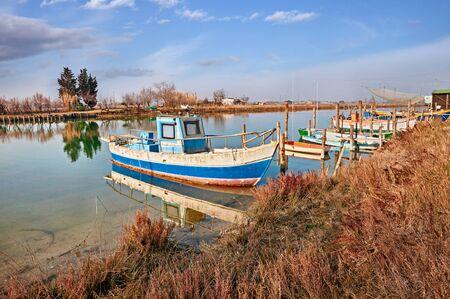 Ravenna, Emilia Romagna, Italien: Landschaft des Feuchtgebiets im Naturreservat Po Delta Park, mit kleinen Fischerbooten im Kanal der Lagune