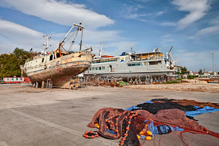 ORTONA, ITALY - SEPTEMBER 14: the dry dock of the port with boat repair shipyard and the fishing nets on the quay. Photo taken on September 14, 2015 in Ortona, Abruzzo, Italy
