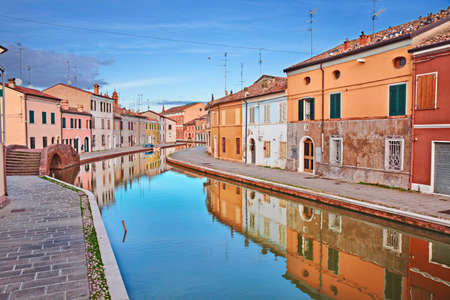 water town: Comacchio, Ferrara, Emilia Romagna, Italy: view of the colored houses with mirror on the water of the canal in the old town known as the Little Venice Stock Photo