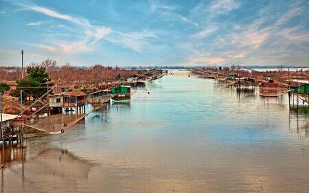 Comacchio, Ferrara, Emilia Romagna, Italy: landscape of the wetland with fishing huts and nets in the lagoon Stock Photo