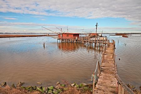 Comacchio, Ferrara, Emilia Romagna, Italien: Landschaft des Feuchtgebietes im Naturschutzgebiet Po Delta Park mit Fischerhütten in der Lagune Standard-Bild