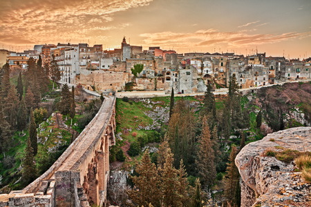Gravina in Puglia, Bari, Italië: landschap bij zonsopgang van de oude stad en de oude brug van het aquaduct (viadotto Madonna della Stella) over het diepe ravijn Stockfoto
