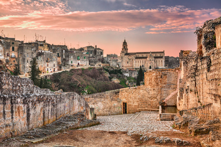Gravina in Puglia, Bari, Italy: landscape at sunrise of the old town with the cathedral seen from the pathway with the source at the entrance of the ancient aqueduct bridge over the ravine Stock Photo