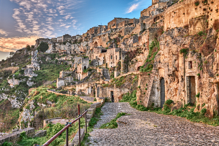 rupestrian: Matera, Basilicata, Italy: landscape at sunrise of the old town (sassi di Matera), with the ancient cave houses carved into the tufa rock over the deep ravine Stock Photo