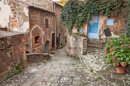 corner house: Sorano, Grosseto, Tuscany, Italy:  picturesque narrow alley with an ancient votive shrine and plants in the old town of the Tuscan medieval village Stock Photo