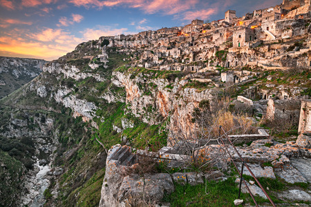 rupestrian: Matera, Basilicata, Italy: landscape at sunrise of the old town (sassi di Matera) with the houses carved into the tufa rock and the creek at the bottom of the deep ravine Stock Photo