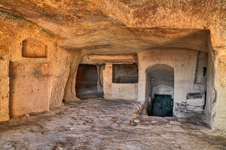 rupestrian: Matera, Basilicata, Italy. interior of an old cave house carved into the tufa rock in the old town. Stock Photo