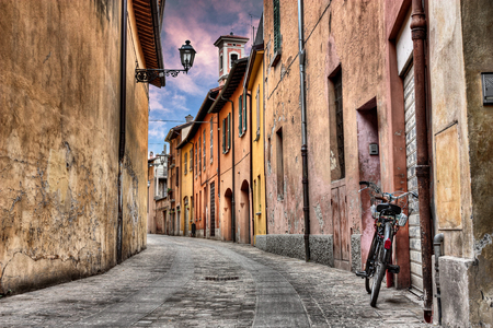 imola: Imola, Bologna, Italy: narrow street at sunset in the old town with bicycle, street lamp, colored houses and bell tower Stock Photo