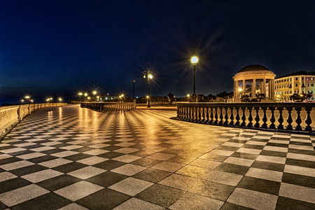 Livorno, Tuscany, Italy: promenade Mascagni Terrace at night, an elegant square on the coast with black and white checkered floor, columned bannister and a round gazebo