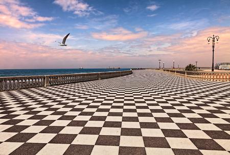 리보 르노, 투스카니, 이탈리아 : 새벽 산책로 마스카니 테라스, 흑인과 백인 바둑판 무늬 포장 도로 및 기둥 형 베니 스터가있는 리구 리아 해 (Ligurian s
