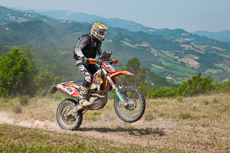 biker riding enduro motorcycles KTM 450 EXC in the green hills during the Italian championship Motorally Terre di Romagna, on July 5, 2015 in Predappio, FC, Italy