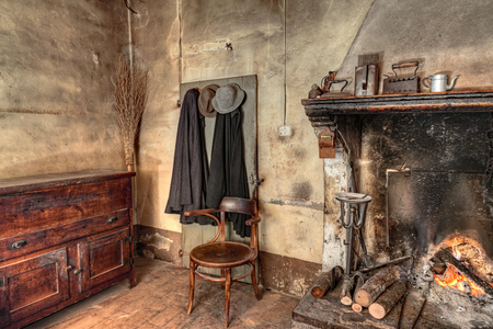 old times farmhouse - interior of an old country house with fireplace, kitchen cupboard, ancient mantles and straw broom Standard-Bild