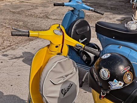 yellow classic scooter Vespa with spare wheel cover parked during the italian scooter rally Raduno Vespa e Lambretta, on June 19, 2016 in Forlimpopoli, FC, Italy