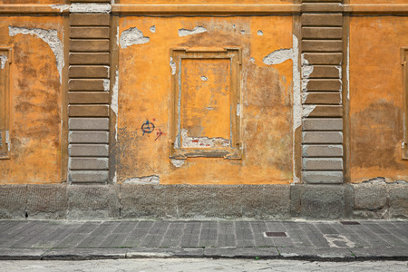 old wall with scratched stained plaster and sidewalk - grunge background with yellow orange pastel paint - urban decay Stock Photo