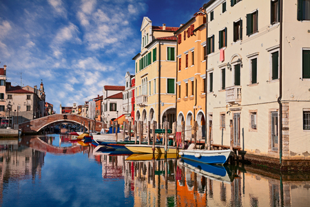 Chioggia, Venice, Italy: canal in the old town with bridge, boats and colorful reflections on the water of the ancient buildings Stock Photo