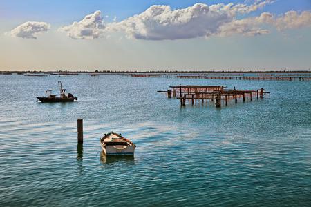 Porto Tolle, Rovigo, Veneto, Italia: paisaje marino del mar Adriático en el Parque del Delta del Po con barcos de pesca y postes de madera para el cultivo de mejillones Foto de archivo - 87182044